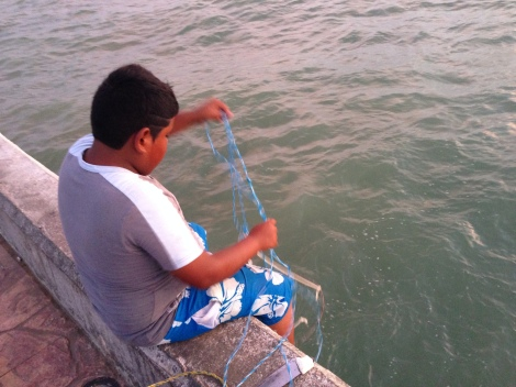 Foto: MugsNoticias. Un niño realiza pesca artesanal en Puerto Progreso, Yucatán. En el malecón, decenas de hombres y mujeres realizan esta práctica a lo largo del día.